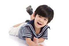 Garçon asiatique mignon se trouvant sur le fond blanc d'isolement Image stock