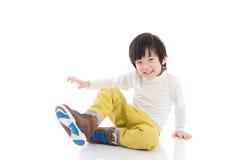 Garçon asiatique s'asseyant sur le fond blanc d'isolement image stock