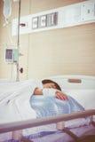 Garçon asiatique se trouvant sur le lit de malade avec l'intravenous salin (iv) santé Photos stock