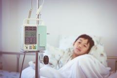 Garçon asiatique se trouvant sur le lit de malade avec le dri de l'intravenous IV de pompe d'infusion Photos libres de droits