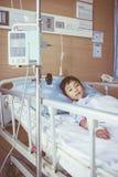 Garçon asiatique se trouvant sur le lit de malade avec le dri de l'intravenous IV de pompe d'infusion Photographie stock