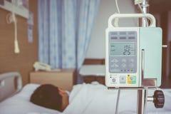 Garçon asiatique se trouvant sur le lit de malade avec le dri de l'intravenous IV de pompe d'infusion Images libres de droits