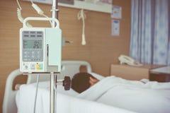 Garçon asiatique se trouvant sur le lit de malade avec le dri de l'intravenous IV de pompe d'infusion Photo libre de droits