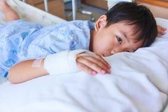 Garçon asiatique se trouvant sur le lit de malade, intravenous salin (iv) en main Images stock