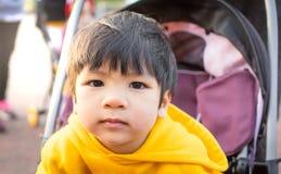 Garçon asiatique sur la poussette photographie stock