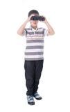 Garçon asiatique tenant des jumelles, d'isolement sur un fond blanc Photos stock