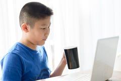 Garçon asiatique tenant la tasse noire tout en à l'aide du comprimé Image stock