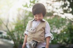 Garçon asiatique tenant le chaton américain de cheveux courts Image libre de droits