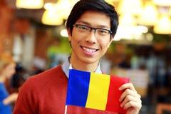 Garçon asiatique tenant le drapeau de la Roumanie Photographie stock libre de droits