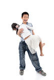 Garçon asiatique tenant sa soeur dans sa main Image libre de droits