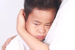 Garçon asiatique triste, pleurant dans son bras de mères photographie stock libre de droits