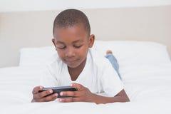 Garçon assez petit à l'aide du smartphone dans le lit Photographie stock libre de droits