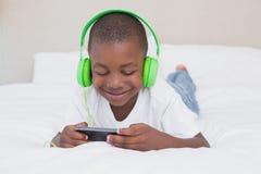 Garçon assez petit employant le smartphone et la musique de écoute dans le lit Photographie stock
