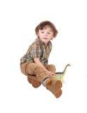 Garçon assez petit s'asseyant sur le plancher Photographie stock