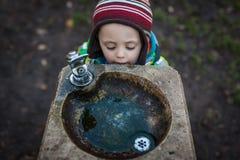 Garçon assoiffé à un poste d'eau potable photo libre de droits