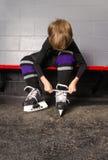 Garçon attachant des patins d'hockey dans le vestiaire Photographie stock libre de droits