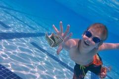 Garçon atteignant le billet d'un dollar Images libres de droits