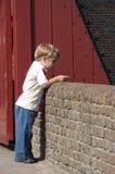 Garçon au mur de château Photographie stock libre de droits