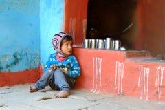 Garçon aux pieds nus d'Indien dans portés des vêtements pauvres se reposant sur le plancher en pierre dans la cuisine asiatique t Photographie stock