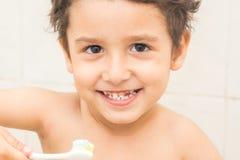 Garçon aux yeux bruns se brossant les dents dans la salle de bains Photo stock