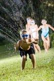 Garçon avec des amis éclaboussant dans l'arroseuse de pelouse Photo libre de droits