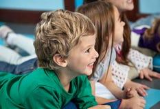 Garçon avec des amis se trouvant sur le plancher dans le jardin d'enfants Images libres de droits