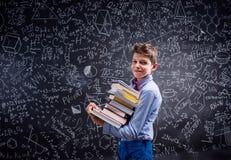 Garçon avec des livres contre le grand tableau noir avec des symboles mathématiques Photographie stock libre de droits