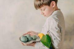 Garçon avec des oeufs de pâques et un perroquet Photo stock