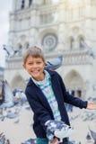 Garçon avec des oiseaux près de cathédrale de Notre Dame de Paris à Paris, France Photos libres de droits