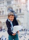 Garçon avec des oiseaux près de cathédrale de Notre Dame de Paris à Paris, France Photographie stock