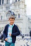 Garçon avec des oiseaux près de cathédrale de Notre Dame de Paris à Paris, France Image libre de droits