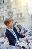 Garçon avec des oiseaux près de cathédrale de Notre Dame de Paris à Paris, France Image stock