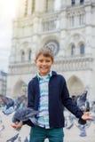 Garçon avec des oiseaux près de cathédrale de Notre Dame de Paris à Paris, France Photos stock