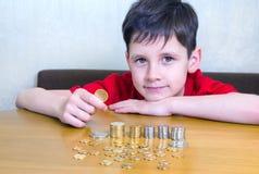 Garçon avec des pièces de monnaie photo stock