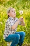 Garçon avec des pissenlits en été Photographie stock