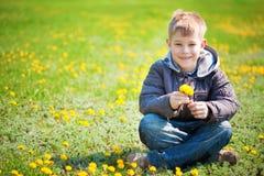 Garçon avec des pissenlits en parc vert. ressort Photo libre de droits