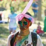 Garçon avec des verres ayant l'amusement pendant le festival de couleur Photo stock