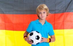 Garçon avec du ballon de football devant le drapeau allemand Photographie stock libre de droits