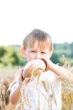 Garçon avec du pain dans le grain Photographie stock