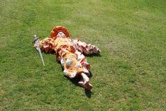 Garçon avec l'épée se trouvant sur l'herbe Photos libres de droits