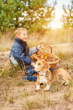 Garçon avec l'animal familier sur la clairière de forêt d'automne Photo libre de droits