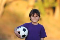 Garçon avec la bille de football au coucher du soleil Photographie stock libre de droits