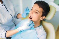 Garçon avec la bouche ouverte dans une chaise dentaire image libre de droits