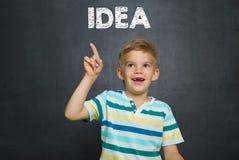 Garçon avec la craie et conseil pédagogique avec l'IDÉE des textes Images stock