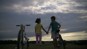 Garçon avec la fille avec des bicyclettes sur la montagne tenant des mains le soir banque de vidéos