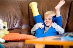 Garçon avec la jambe cassée dans la fonte se reposant sur le divan Images stock