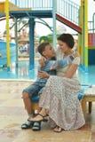 Garçon avec la mère sur le terrain de jeu Image libre de droits