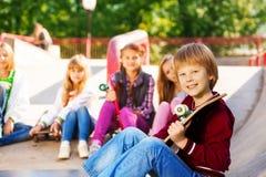 Garçon avec la planche à roulettes et ses amis s'asseyant derrière Photographie stock libre de droits