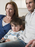 Garçon avec la télévision d'And Mother Watching de père à la maison Photographie stock libre de droits
