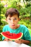 garçon avec la tranche de pastèque sur le fond de jardin d'été Photographie stock